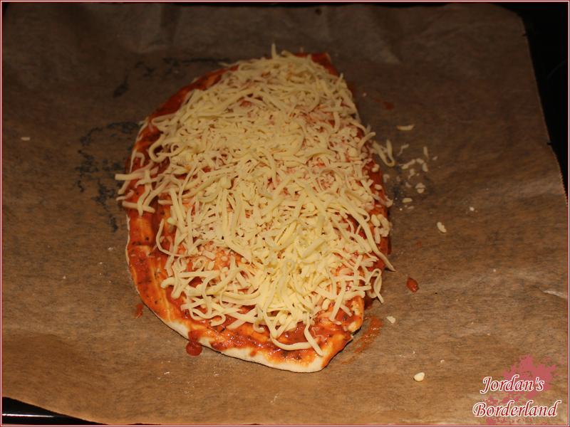 Blech legen, mit Sauce bestreichen und mit Käse bestreuen