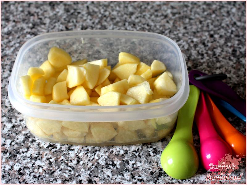 Apfel schälen, schneiden und mit Zitronensaft mischen
