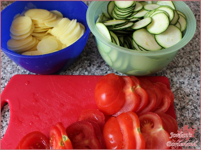 Kartoffeln schälen, Tomaten und Zucchini putzen. Alles in Scheiben schneiden